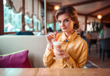 Attractive woman drinks a cocktail from the straw