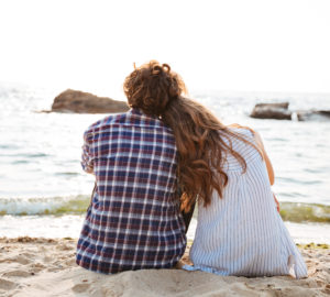 Beautiful young couple sitting together on the beach