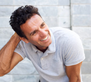 Handsome older man laughing with hand in hair