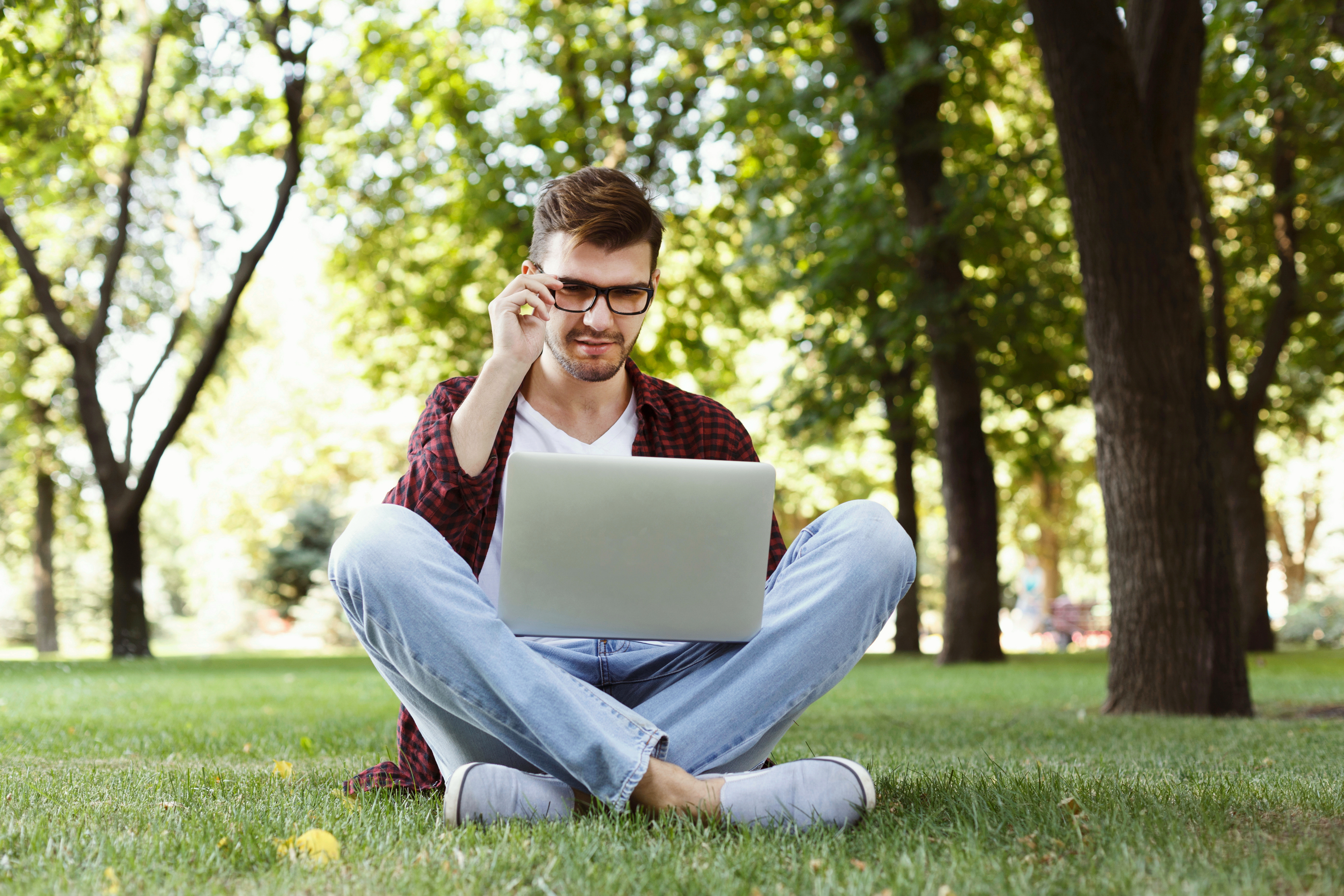 Man working outdoors on laptop. Preparing for exams, sitting on grass at university campus park. Technology, communication, education and remote working concept, copy space
