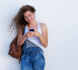 Portrait of happy young girl on cellphone texting