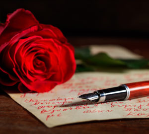 Red rose and an ink pen on a handwritten letter