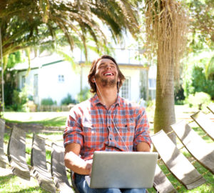 Young man laughing with laptop outdoors