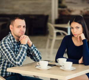 Young unhappy married couple having serious quarrel at cafe