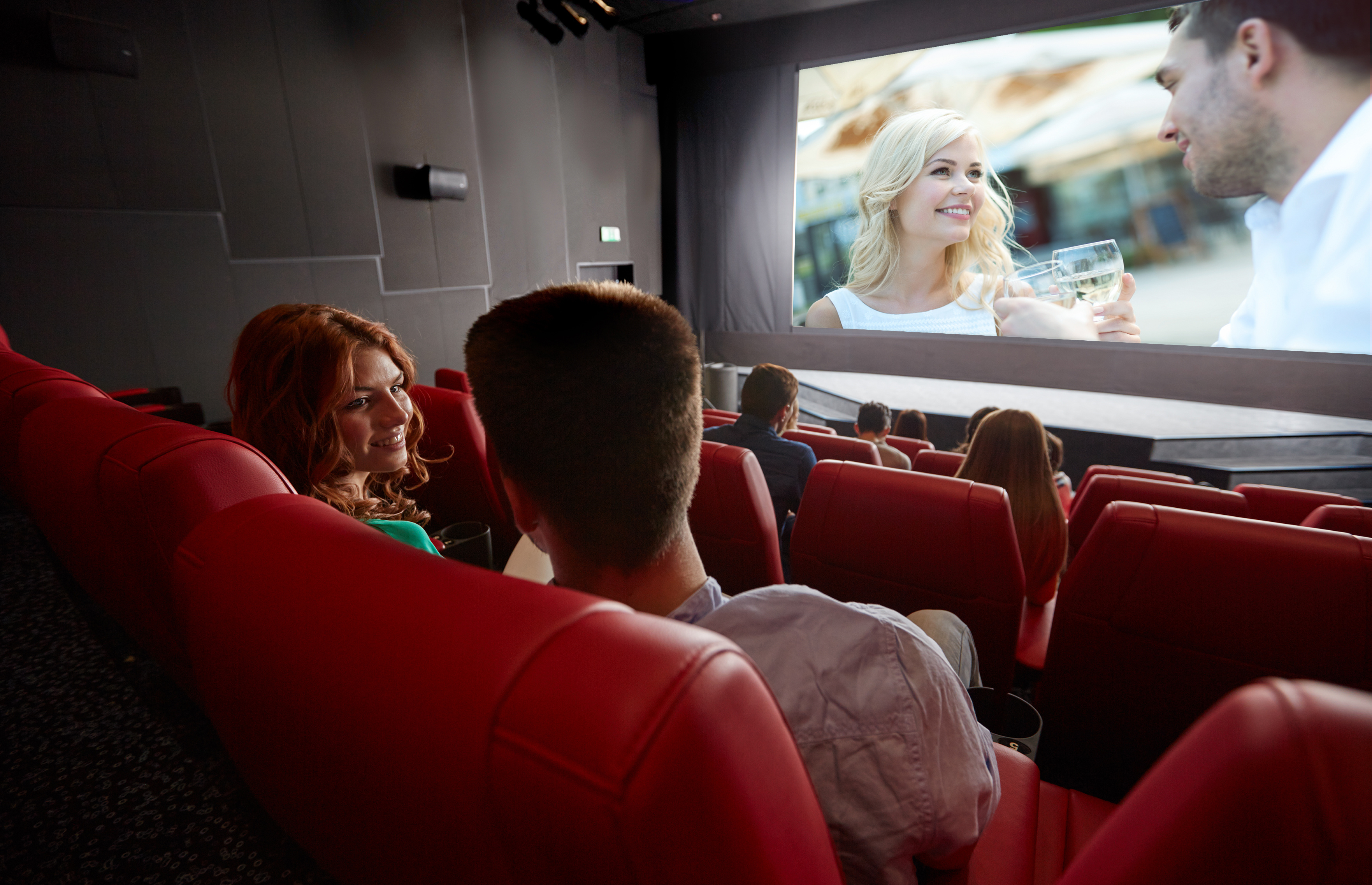happy couple watching movie and talking in theater